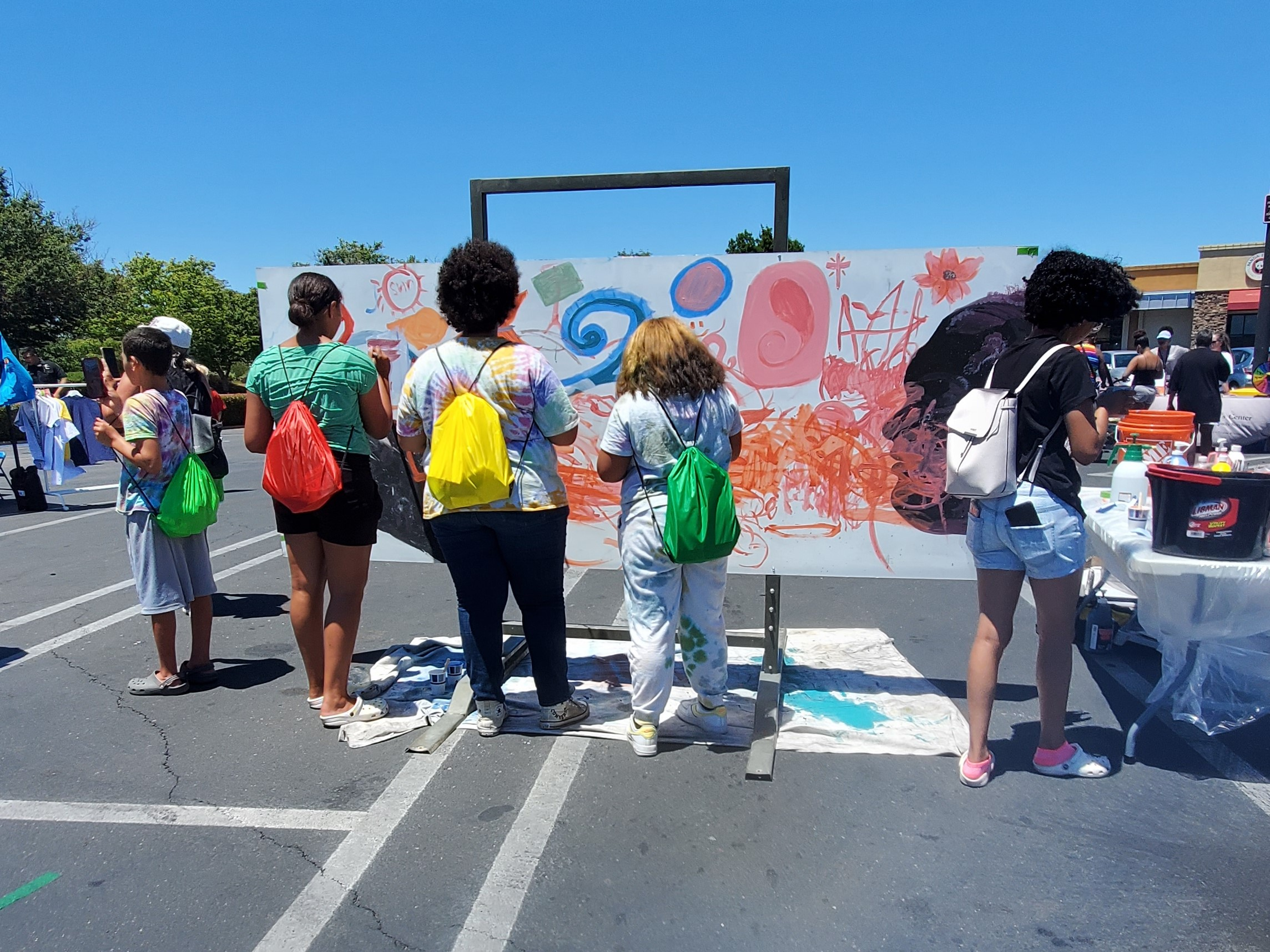 several youth gather around a public art wall I installed on a portable platform. they used brushes on aluminum panels and created a colorful and beautiful piece